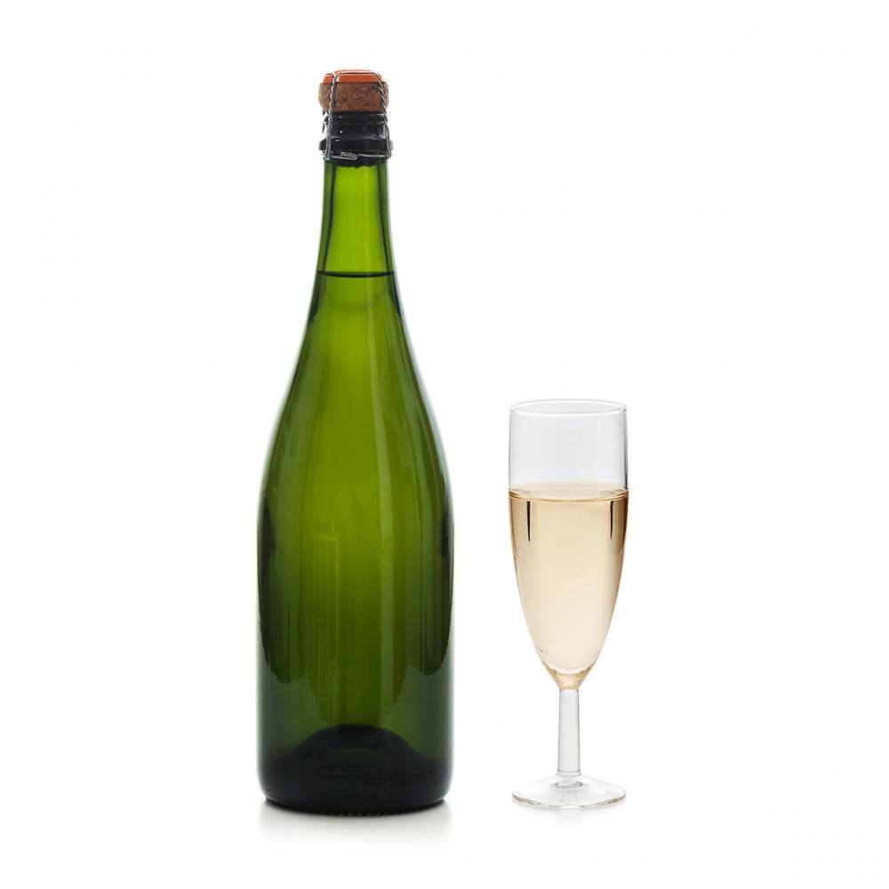 Imagen en la que se ve una botella de cava con una copa a su lado con cava en su interior