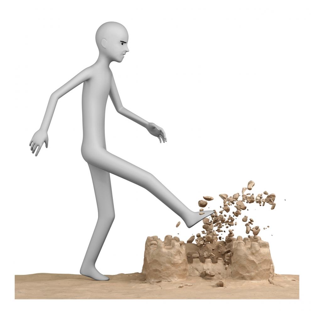 Imagen en la que sale una persona destrozando un castillo de arena de una patada