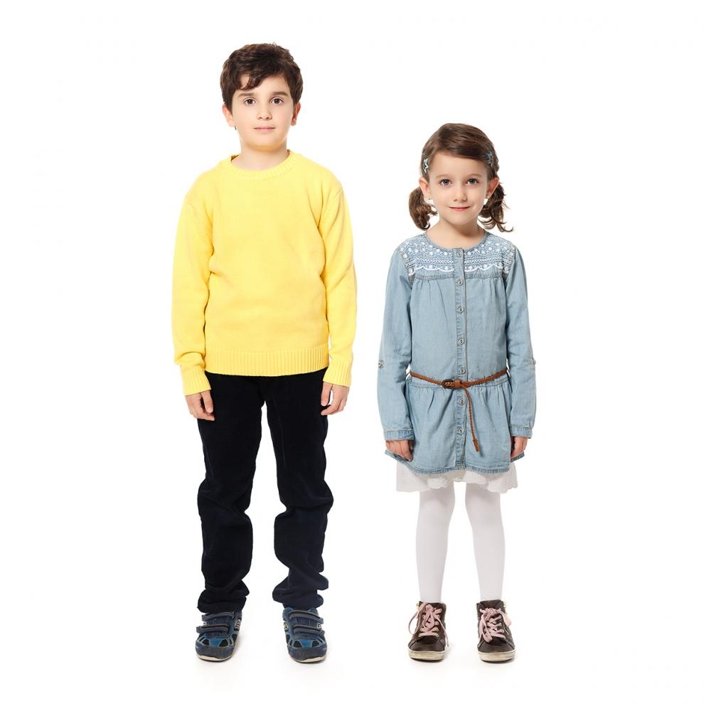 Imagen en la que se ven un niño y una niña pequeños de cuerpo entero