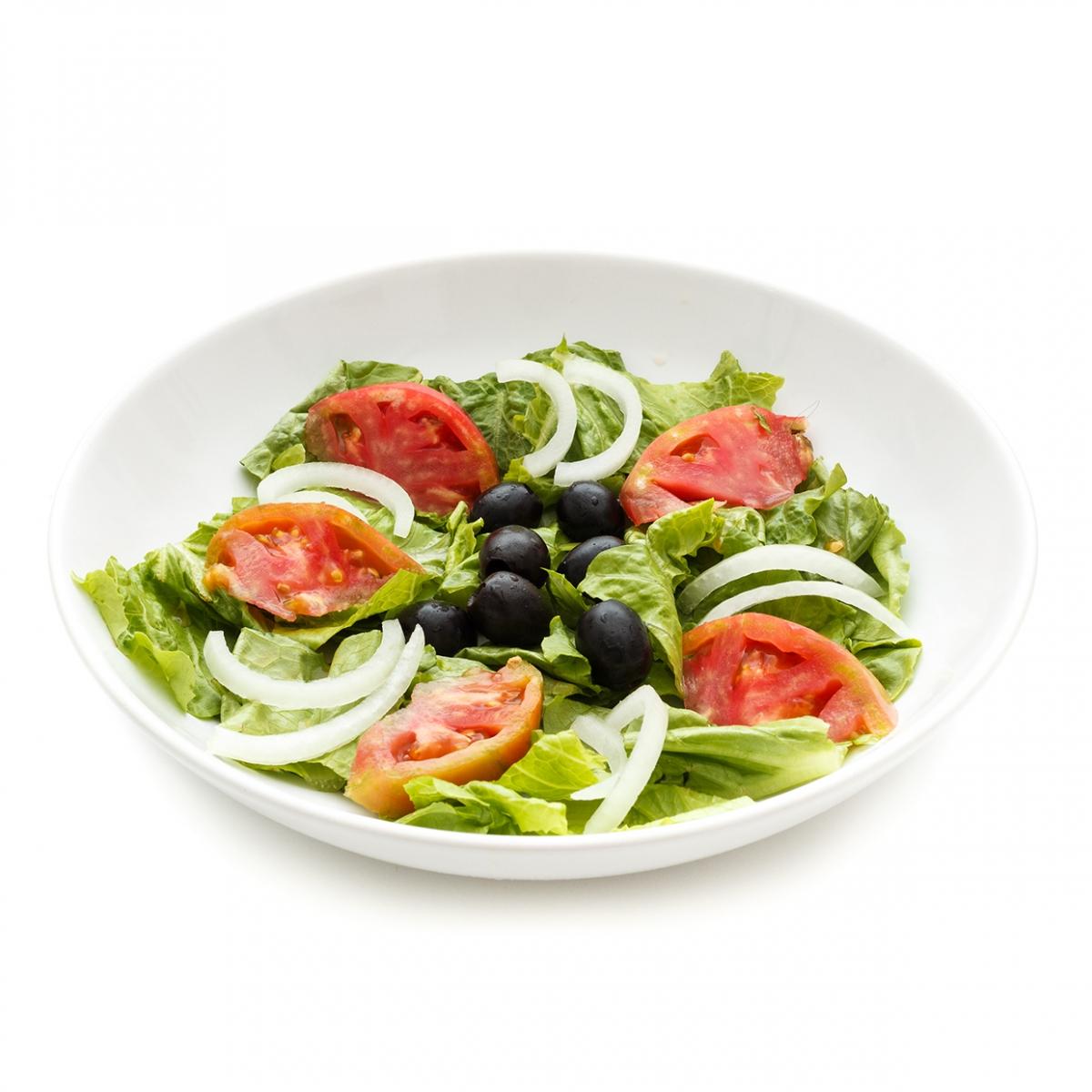 Imagen en la que se ve un plato de ensalada compuesta por lechuga, tomate, cebolla y olivas