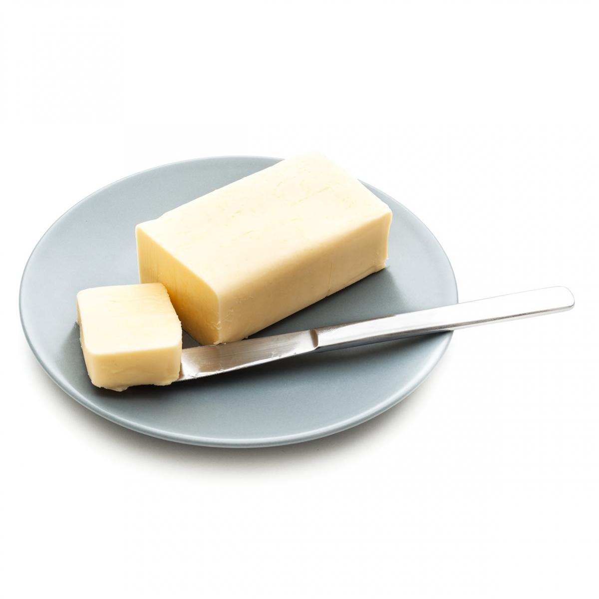 Imagen en la que se ve un bloque de mantequilla sobre un plato y con un trozo cortado encima de un cuchillo