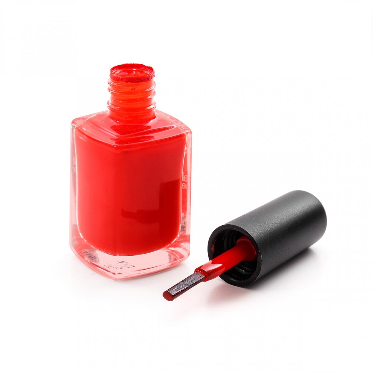 Imagen en la que se ve un frasco de esmalte de uñas de color rojo