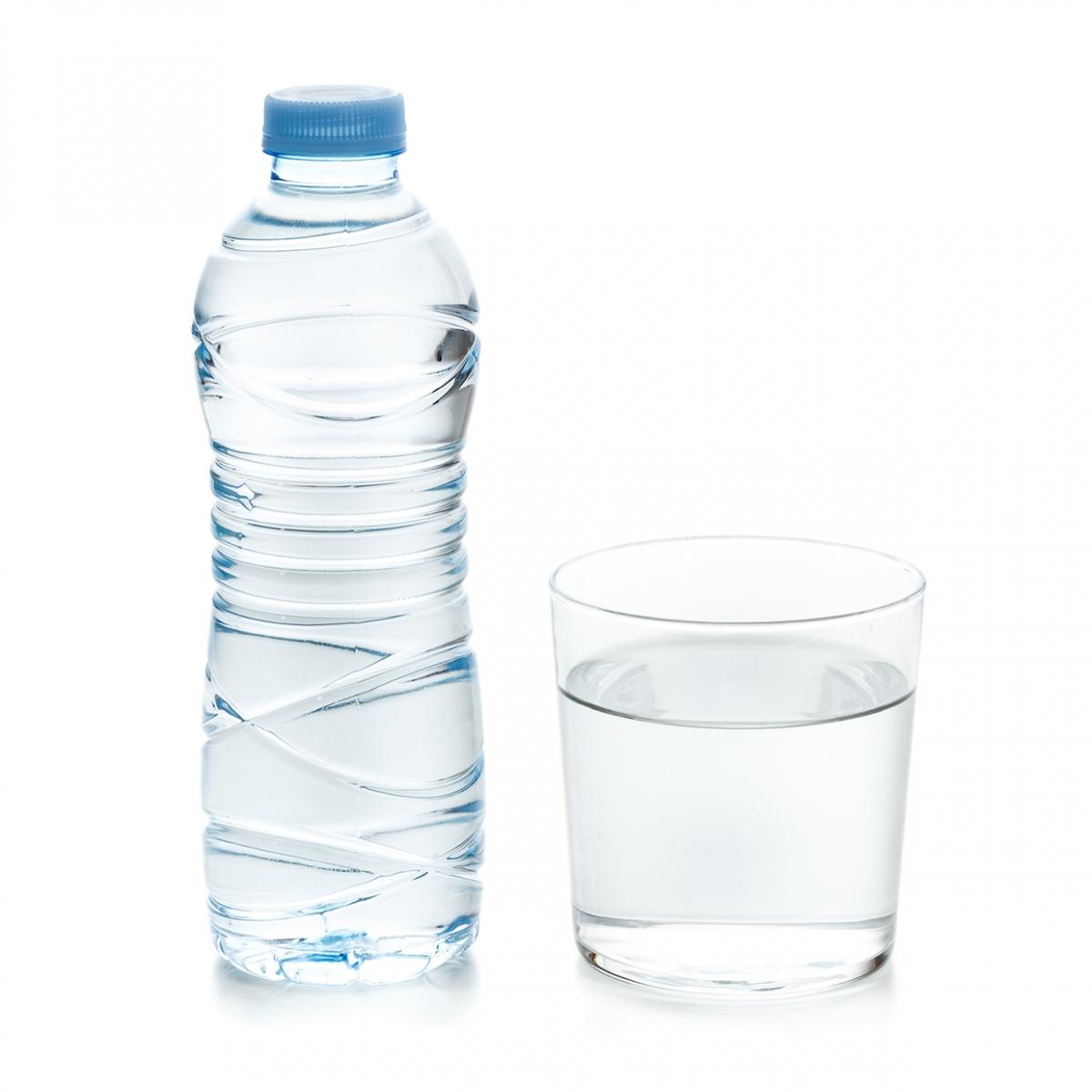 Imagen en la que se ve una botella de plástico llena de agua con un vaso lleno de agua a su lado