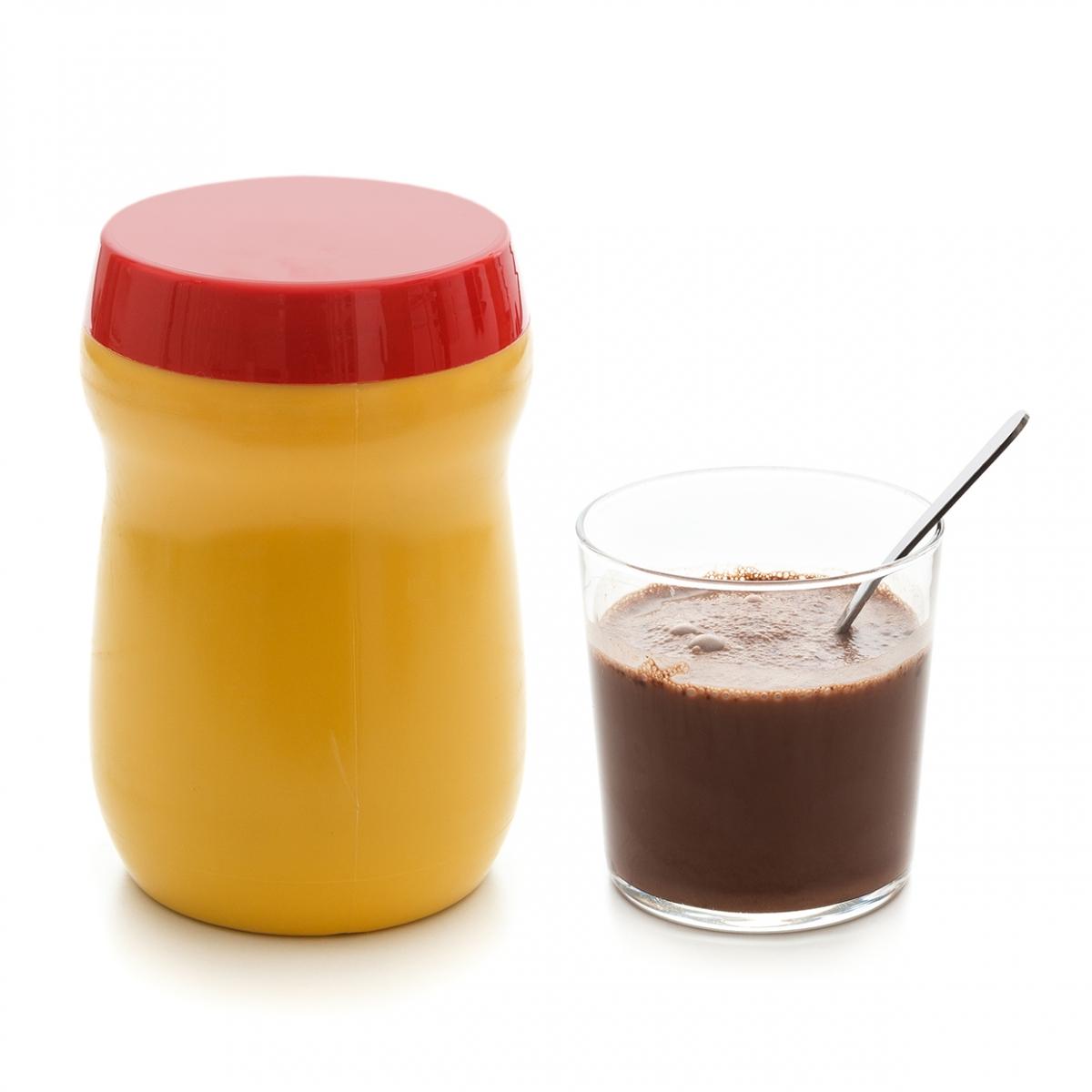 Imagen en la que se ve un bote de cacao con un vaso a su lado con cacao y una cucharilla en su interior