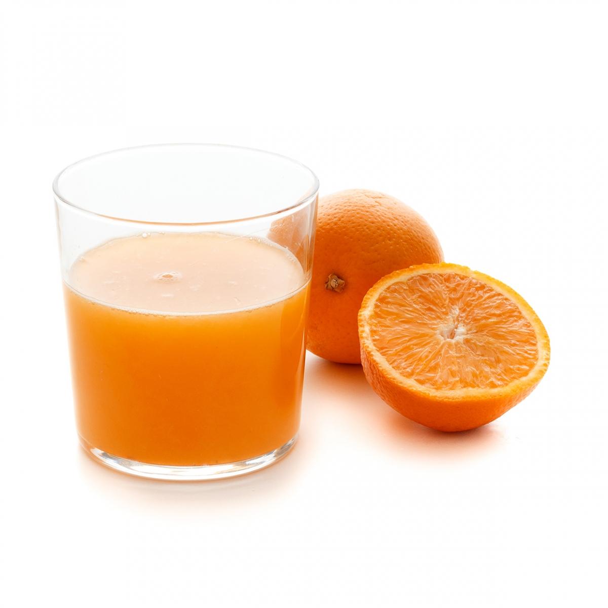 Imagen en la que se ve un vaso con zumo de naranja y, a su lado, una naranja entera y otra partida por la mitad delante.