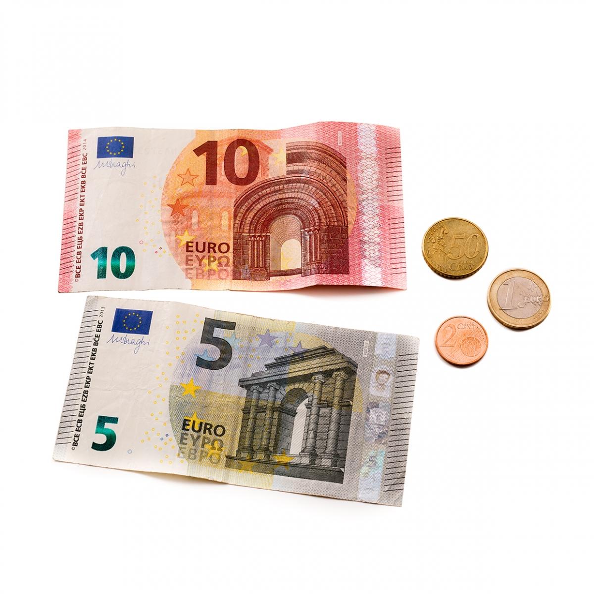 Imagen en la que se ven dos billetes y tres monedas