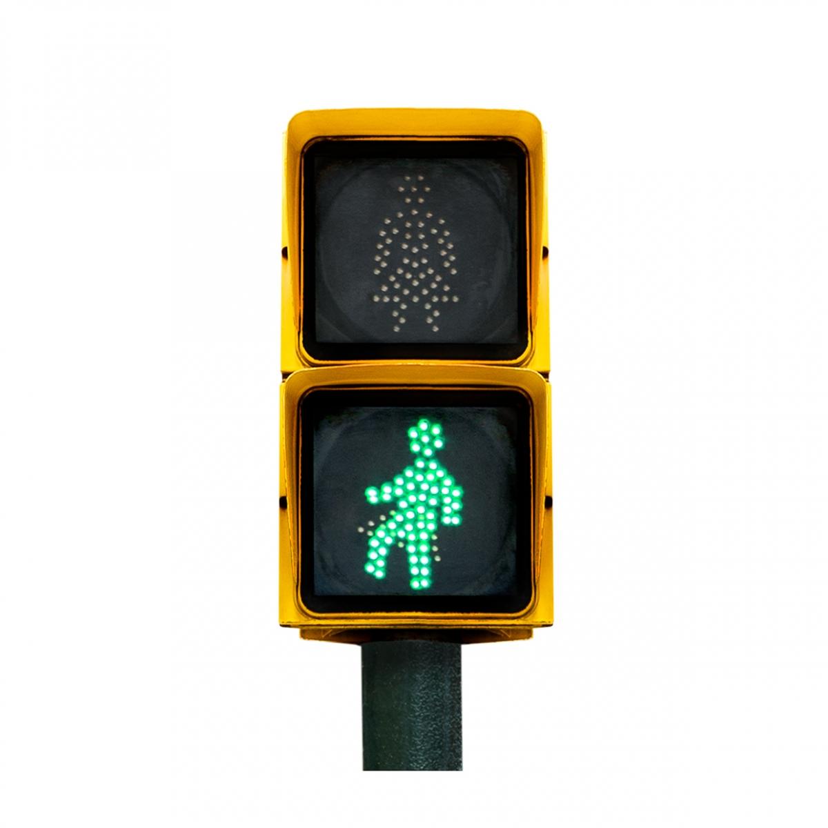 Imagen en la que se ve un semáforo de peatones con la luz verde iluminada