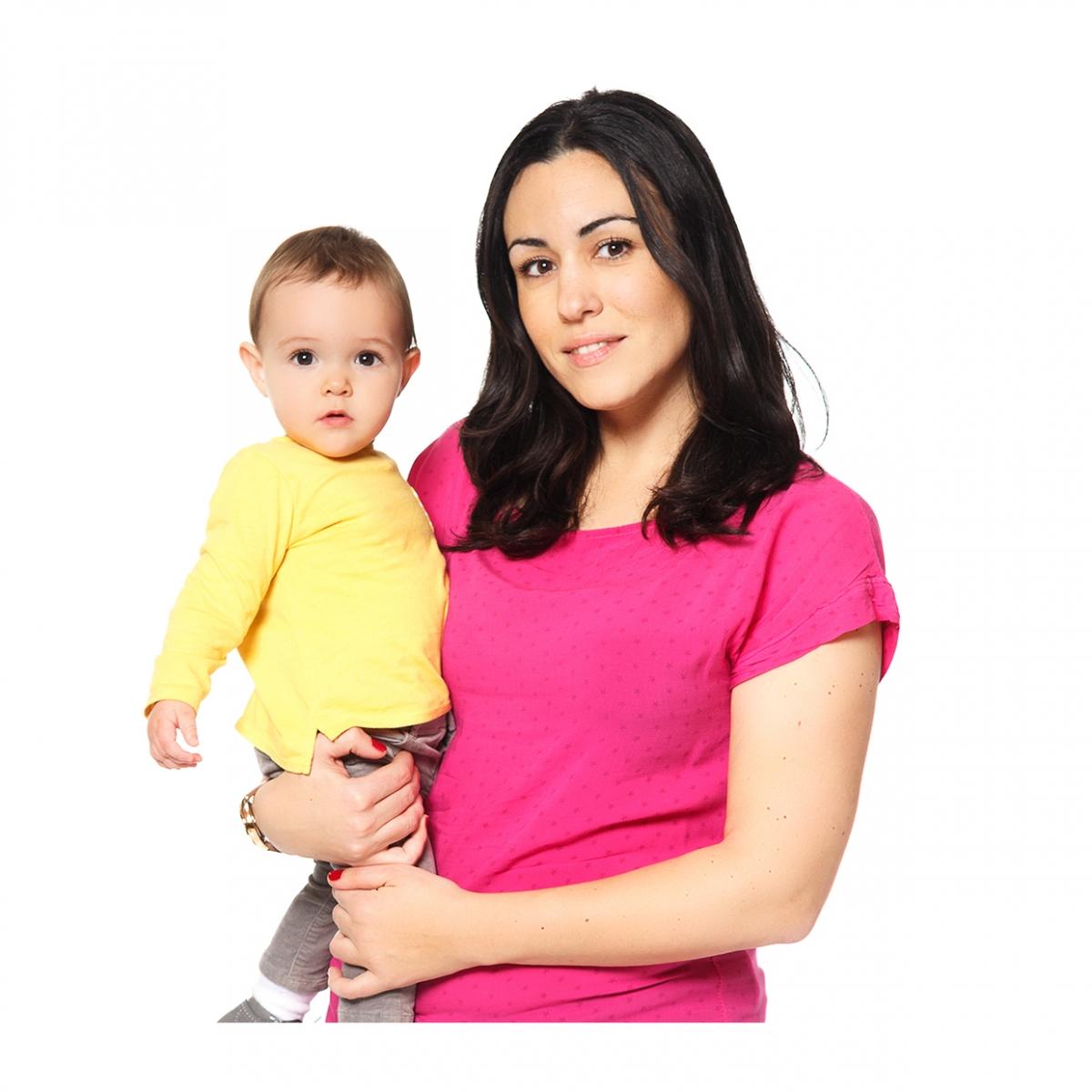 Imagen en la que se ve una madre sosteniendo a su hijo en brazos en medio cuerpo