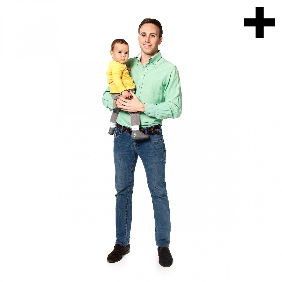 Imagen en la que se ve un padre sosteniendo a su hijo en brazos de cuerpo entero