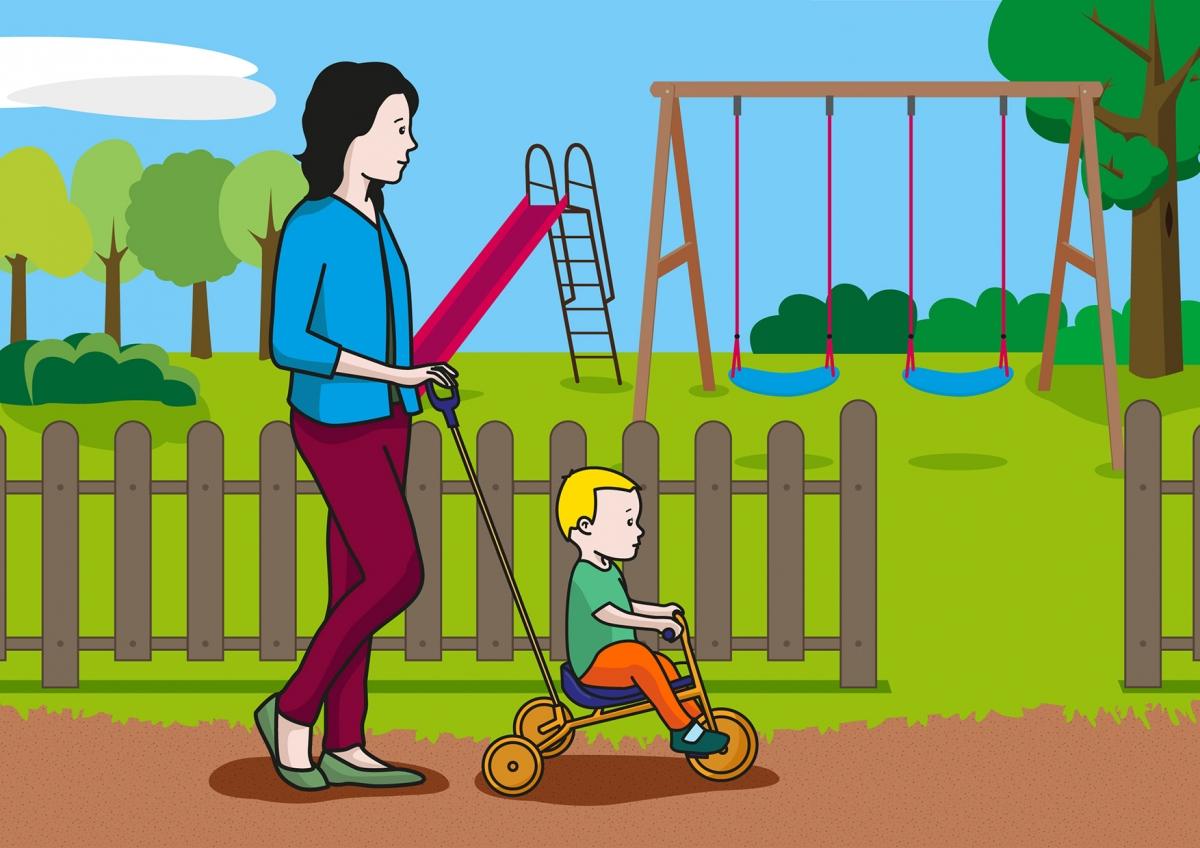 En la escena, se observa a un bebé, montado en un triciclo y acompañado de su madre, dirigiéndose al parque.