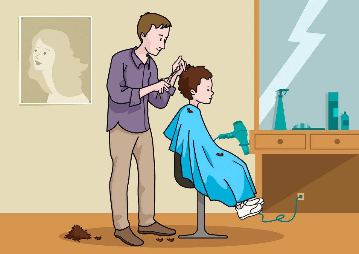 El peluquero corta el pelo al niño