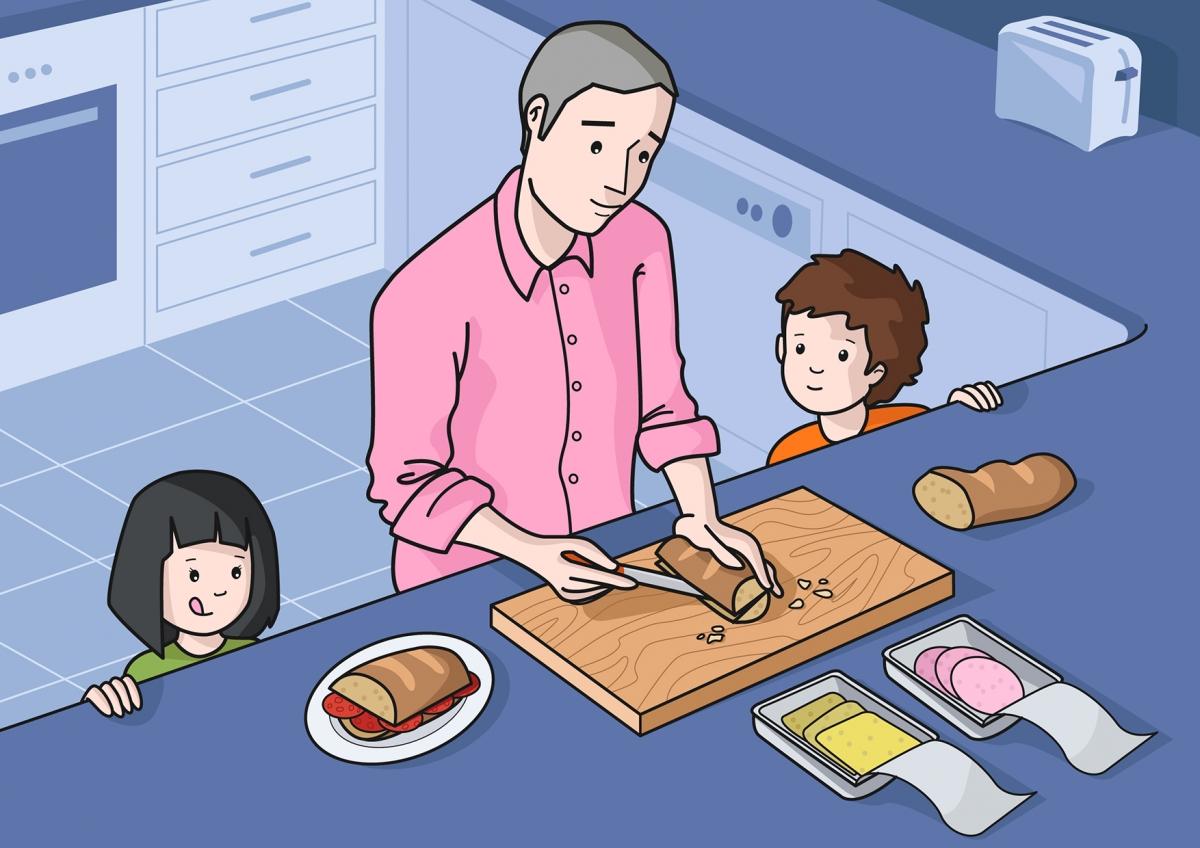 El  papá corta el pan para hacer un bocadillo a los niños