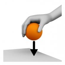Imagen en la que se ve una mano cogiendo una pelota naranja de una superficie