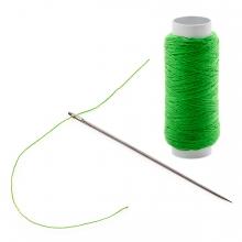 Imagen en la que se ve una aguja y un carrete de hilo verde