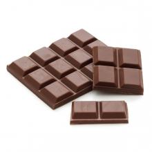 Imagen en la que se ve una tableta de chocolate negro y porciones de cuatro y dos delante y encima de ella