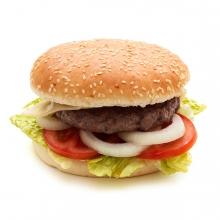 Imagen en la que se ve un panecillo redondo con una hamburguesa dentro y guarnición de lechuga, tomate y cebolla