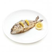 Imagen en la que se ve un pescado cocinado con limón sobre un plato