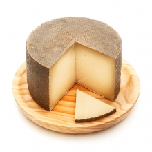 Imagen en la que se ve un queso al que le falta un cuarto. Delante de él hay una loncha de queso.
