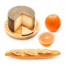 Imagen en la que se ve un queso, una barra de pan y una naranja
