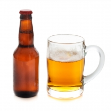 Imagen en la que se ve una botella de cerveza con una jarra a su lado con cerveza en su interior