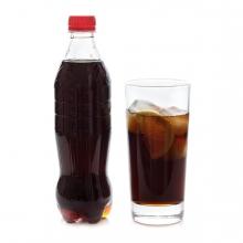 Imagen en la que se ve una botella de cola con un vaso a su lado con cola en su interior