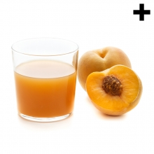 Imagen en la que se ve un vaso con zumo de melocotón y, a su lado, un melocotón entero y otro partido por la mitad delante.