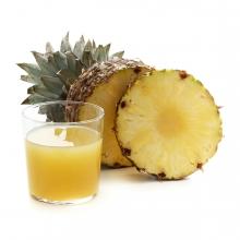 Imagen en la que se ve un vaso con zumo de piña y, a su lado, una piña entera y una rodaja delante.