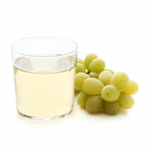 Imagen en la que se ve un vaso con zumo de uva y, a su lado, un racimo de uvas