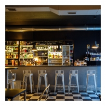 Imagen en la que se ve una barra de bar con banquetas delante