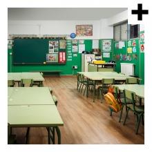 Imagen en la que se ve una clase compuesta por mesas, sillas y una pizarra al fondo