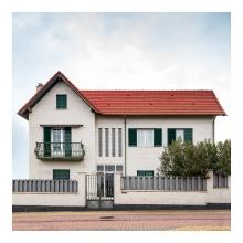 Imagen en la que se ve una casa de dos plantas y ático con una valla en el frente