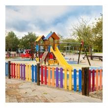 Imagen en la que se un parque infantil y árboles al fondo