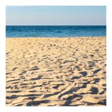 Imagen en la que se ve una playa de arena con el mar al fondo