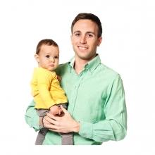 Imagen en la que se ve un padre sosteniendo a su hijo en brazos