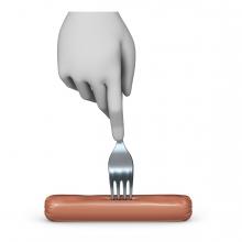 Imagen en la que se ve una mano pinchando una salchicha con un tenedor