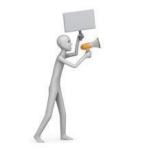 Imagen en la que sale una persona protestando con una pancarta y un megáfono