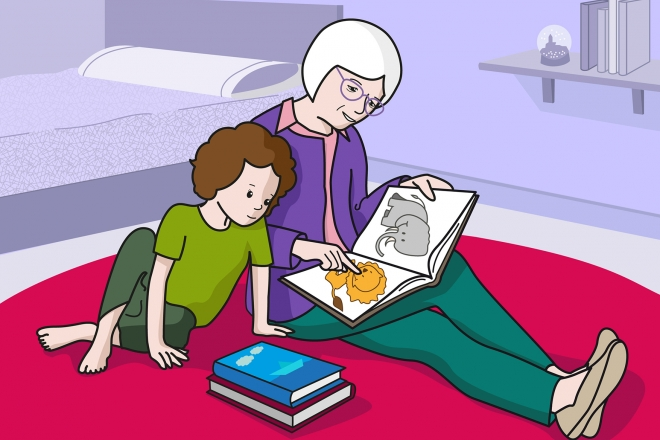 En la escena, se observa a una persona mayor leyendo un cuento a una niña, sentadas en la alfombra.
